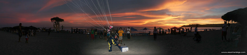 Skydiver grabbing bottle of beer panorama, Puerto Escondido, Mexico