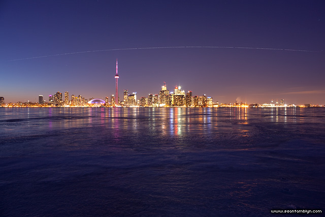 STS-133 space shuttle Discovery and the ISS in orbit over the Toronto skyline
